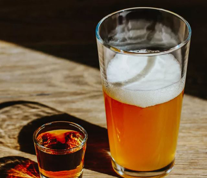 A glass of beer with a whiskey shot