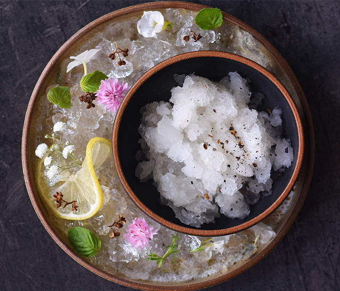 Granita with ice and lemon in a bucket with flowers