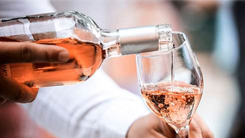 A man pouring a glass of rose