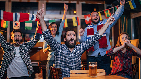 A group of people watching sports in a bar