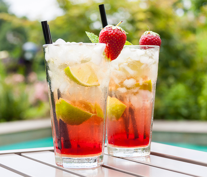 Two gin cocktails with lime wedges and strawberries on a wooden table