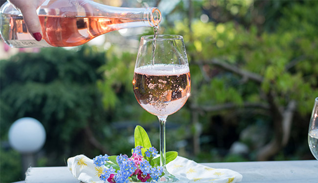 Woman pouring a glass of blush wine