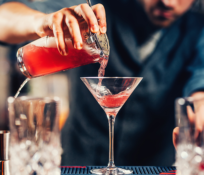 Bartender pouring cocktail into martini glass