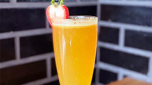 A beer cocktail with strawberry slice