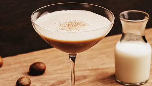 Brandy Alexander cocktail with grated nutmeg on a wooden table