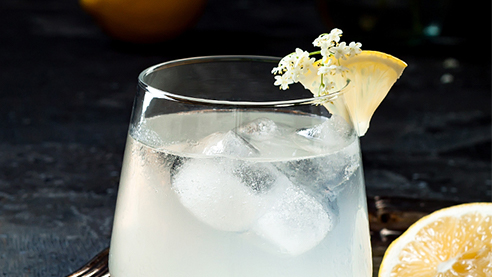 Chartreuse colada with ice and lemon wedges on a table
