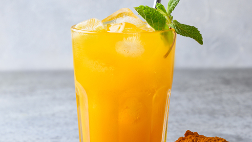 Turmeric cocktail with ginger and turmeric powder on a table