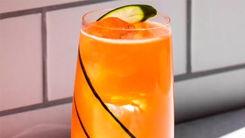 Orange cocktail with a cucumber slice