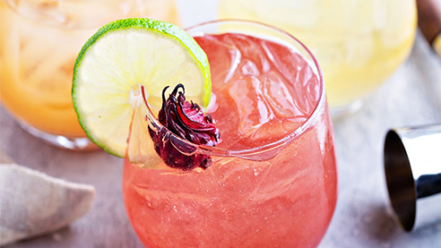 Glass of hibiscus sangria with lime and dried hibiscus flower