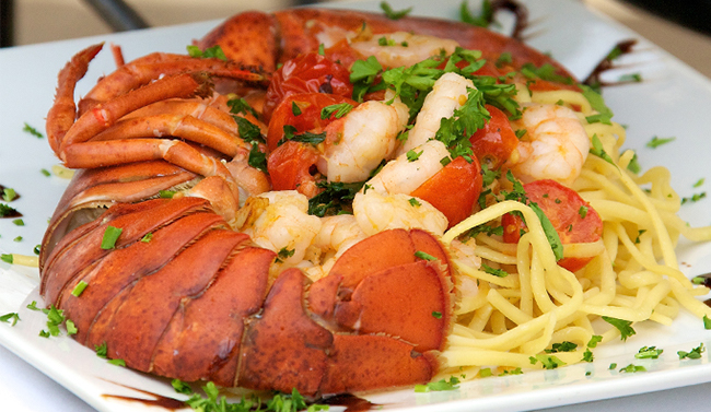 Lobster tail with pasta on a white plate