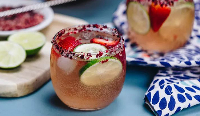 Sparkling margarita rose punch with lime wheels and strawberries