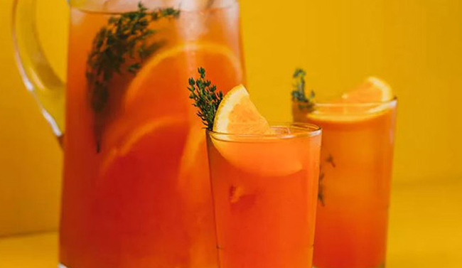 Two glasses and a jug of summer thyme screwdriver against a orange backdrop