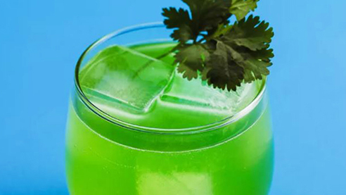 Green cocktail with cilantro against a blue backdrop