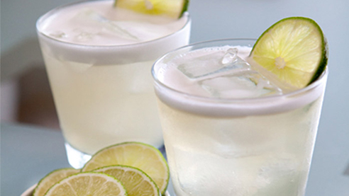 Two glasses of smoky paloma cocktails with lime