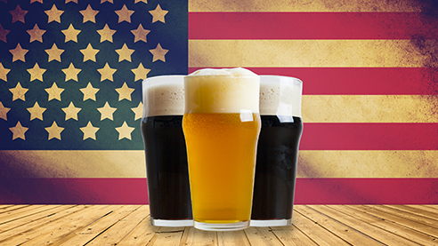 Glasses of beer against an American flag backdrop