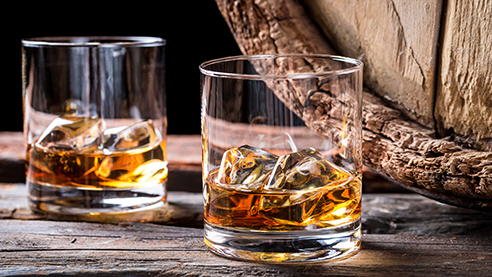 Glasses of brandy with barrels in the background