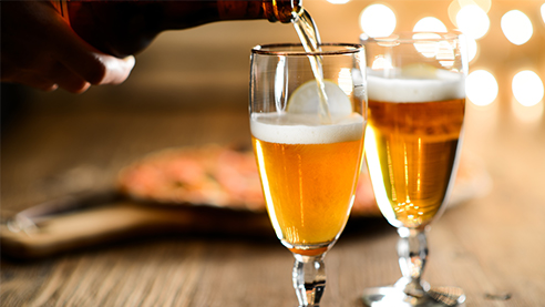 Two glasses of lager on a wooden table